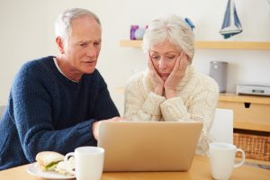 Senior Couple With Financial Problems Looking At Laptop With Worried Exspressions