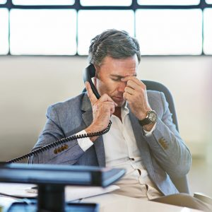 hot of a mature businessman looking stressed while talking on the phone