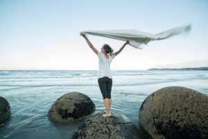 Young woman stands on a boulder at Moeraki boulders, holds a blanket in the air.